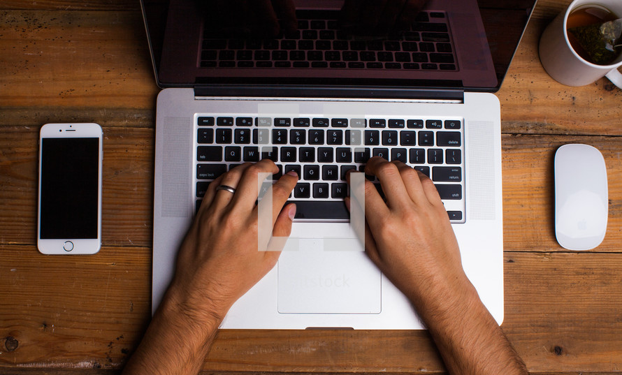 hand typing on a laptop computer