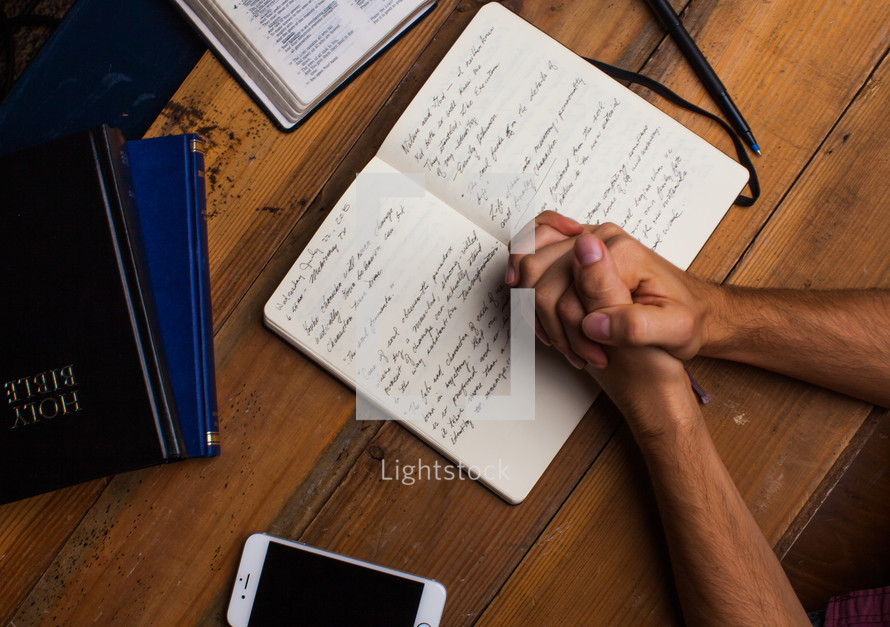 man with praying hands over a journal at a Bible study