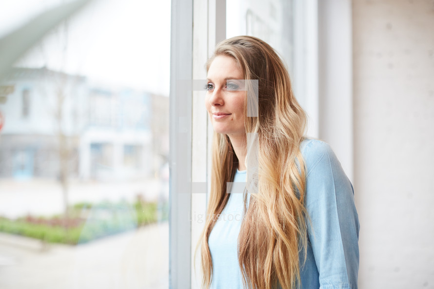 a woman standing in front of a window day dreaming