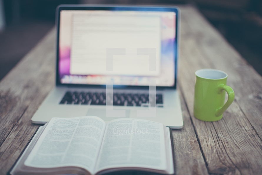 open Bible, computer screen, and coffee mug