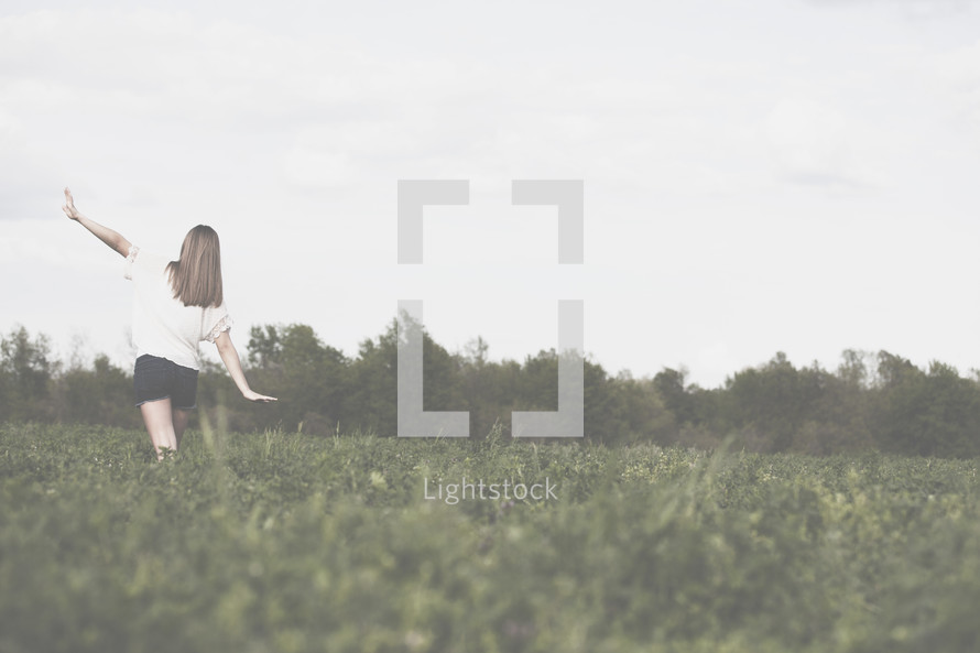 Woman walking through field with arms extended.
