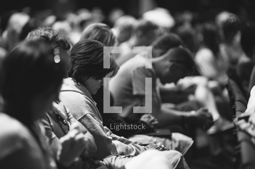 heads bowed in prayer at a worship service