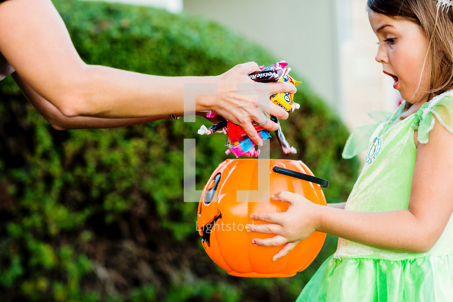 a girl child trick-or-treating getting lots of candy