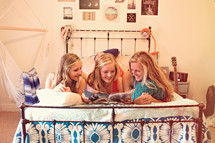 sisters reading a magazine on a bed