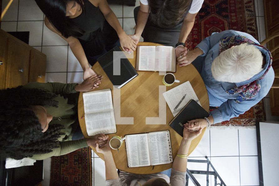 woman's group Bible study holding hands in prayer around a table