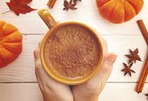 warming hands on a mug of pumpkin spiced coffee
