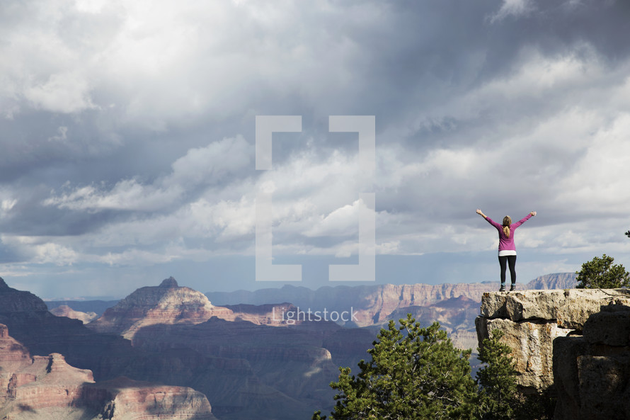 a woman standing at the edge of a cliff with raised arms.
