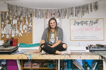 a young woman sitting in a craft room