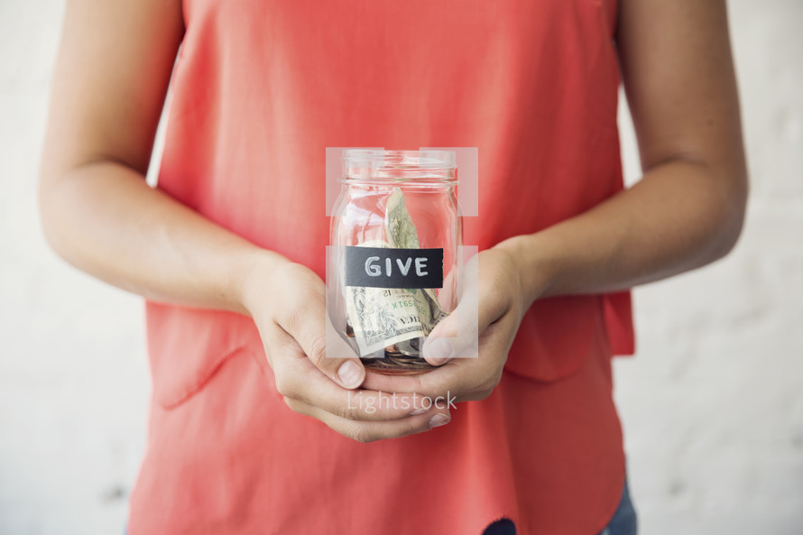 woman holding a give money jar