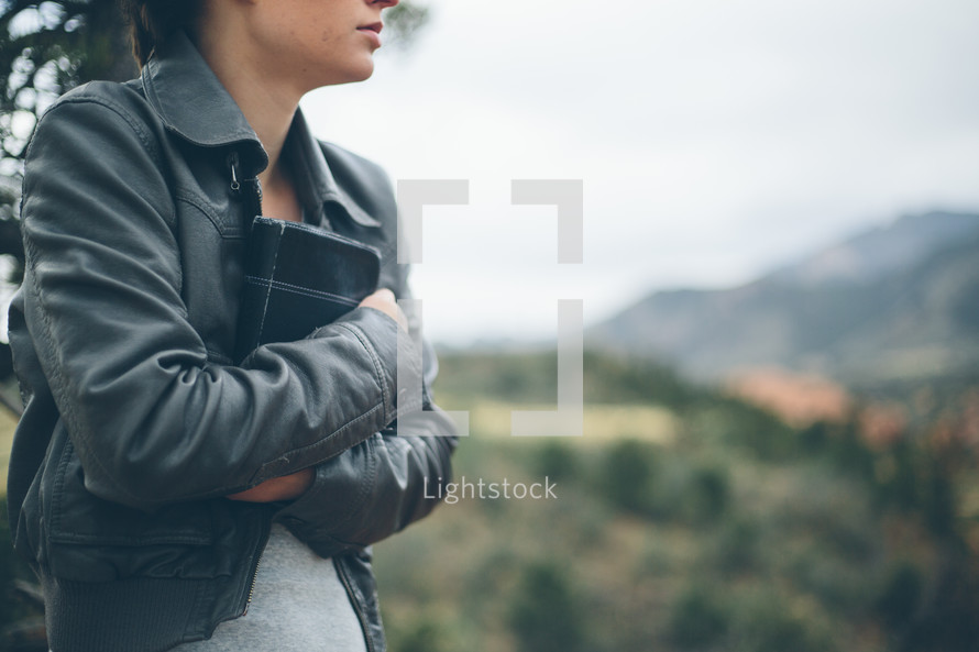 Woman standing outside clutching a Bible.