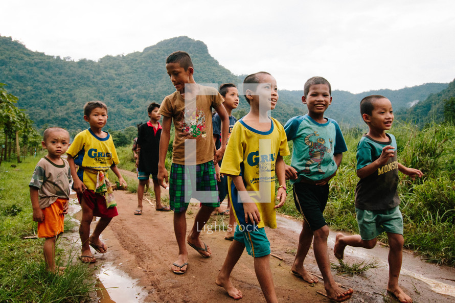 barefoot children walking to school on a dirt road