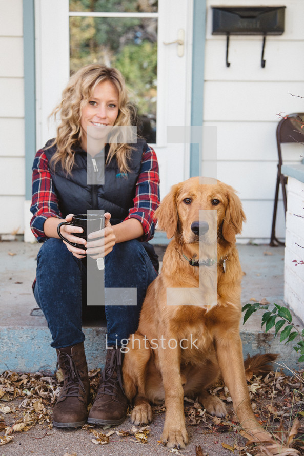 a woman sitting on a stoop in front of her house with a mug of tea and her dog