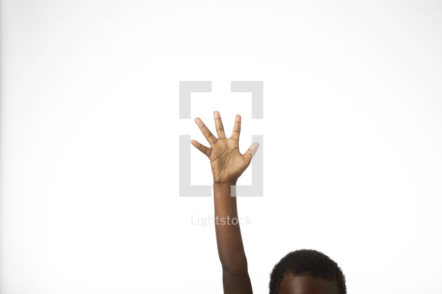 An African American boy with hand raised against a white background