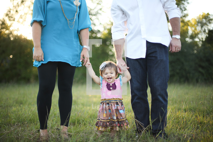 Toddler girl standing in a field of grass holding her parents' hands.