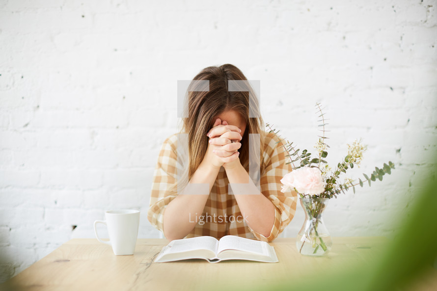 a woman praying over a Bible