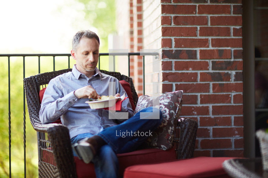 a man sitting on a porch eating a snack