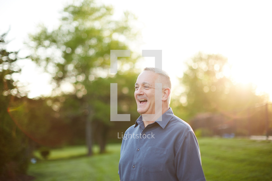 a man laughing outdoors