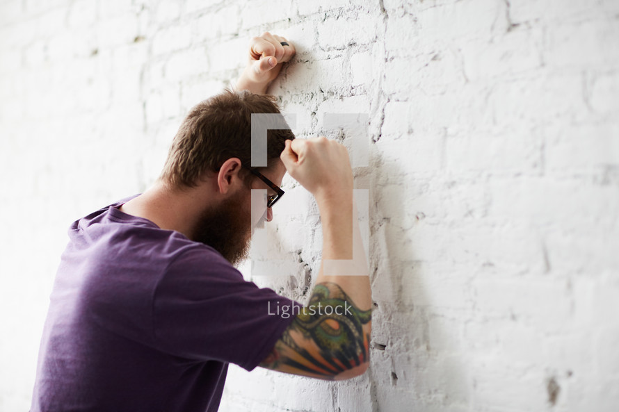 a man beating his fists against a wall