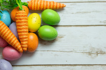 Easter eggs and carrot decorations on wood