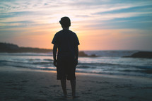 Silhouette of a young man standing on a beach at dusk | Youth | Facing Forward  | Praying | Sun | Faith | Children | Clouds | Courage | Determination | Mediation | Nature | Landscape | Peace