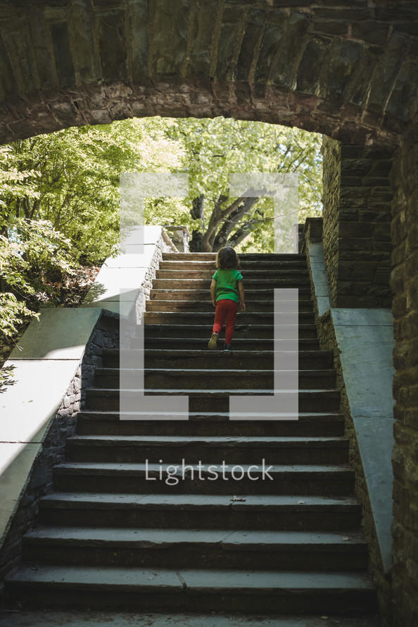 toddler girl exploring stone steps