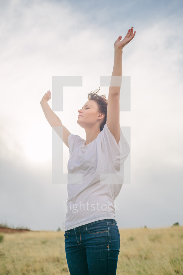 Woman standing outside with arms raised in praise.