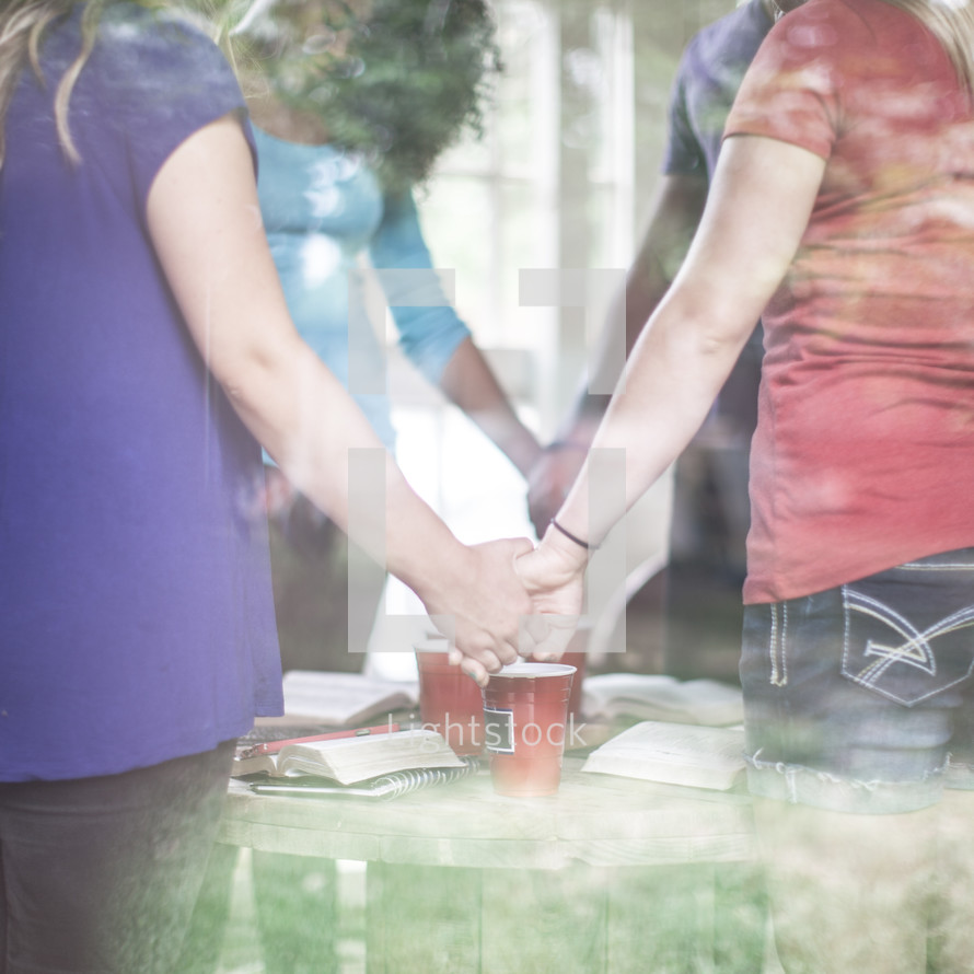 holding hands in a prayer circle at a Bible study