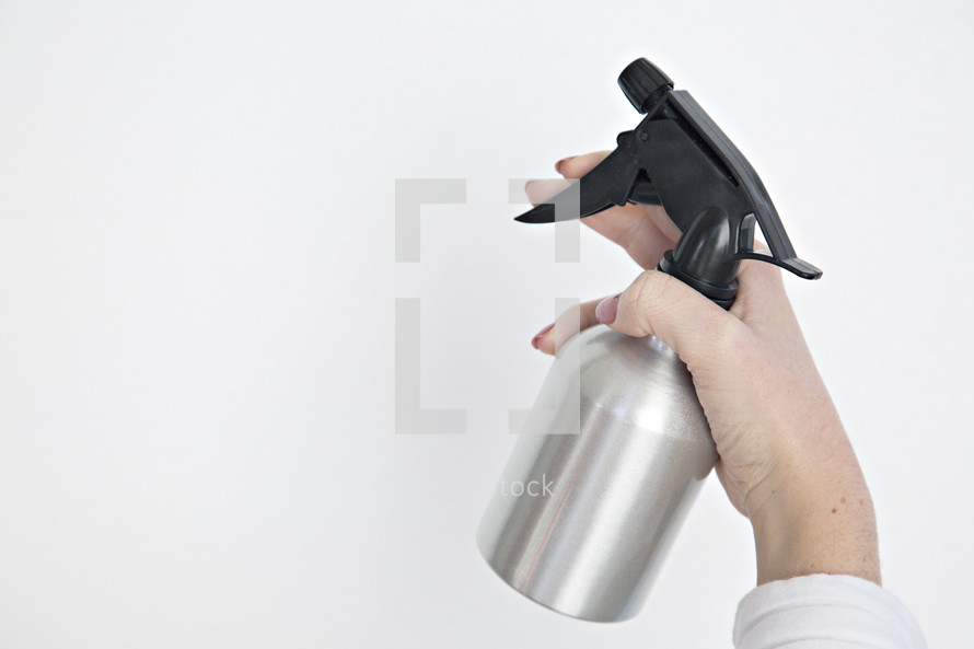 a woman holding a spray bottle