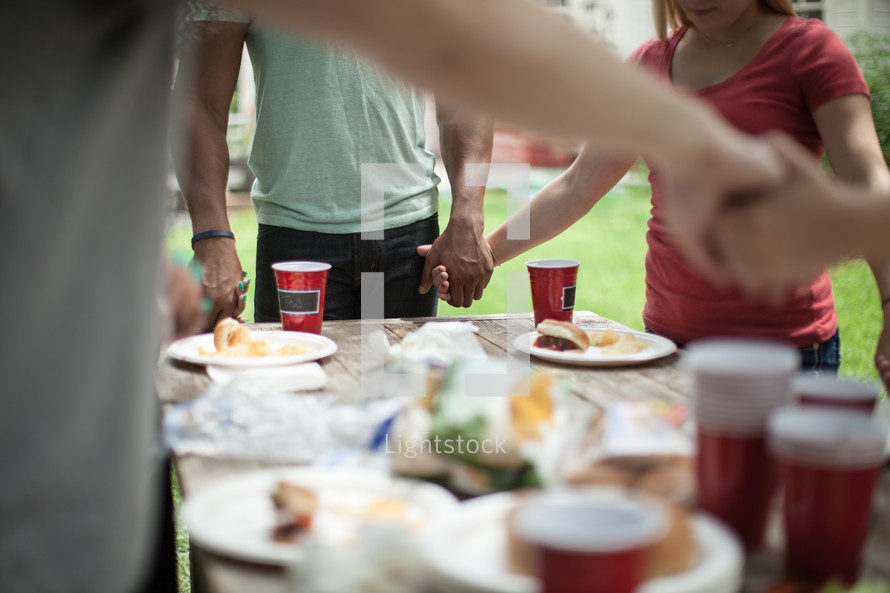 holding hands in prayer above a table of food