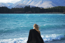 a woman standing on a shore looking out at the water and mountains