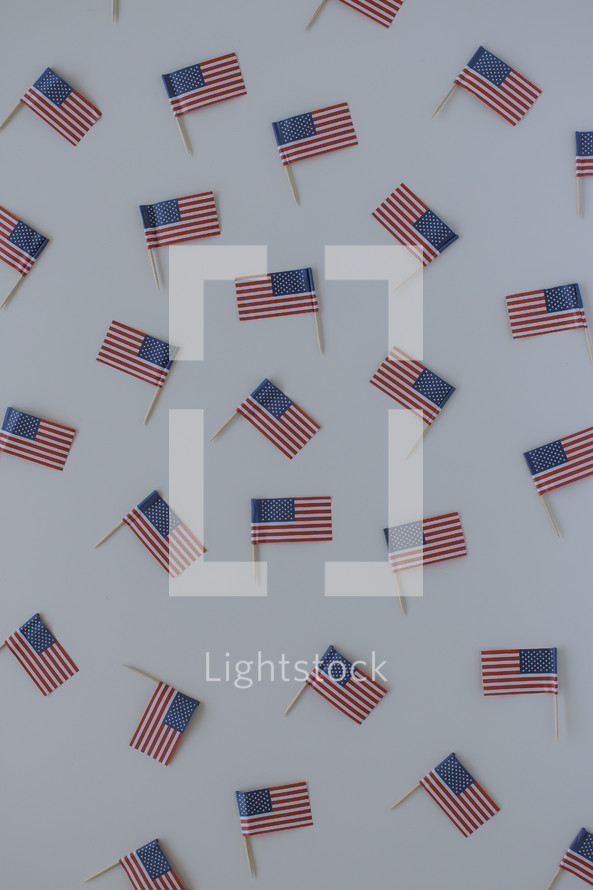Small American flags scattered on a white background.