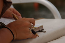 A woman's hands holding a book and pen.