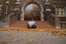 A man sits alone on the bottom step outside of a church