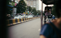 motorcycles, cars, and pedicabs on the streets of Cambodia
