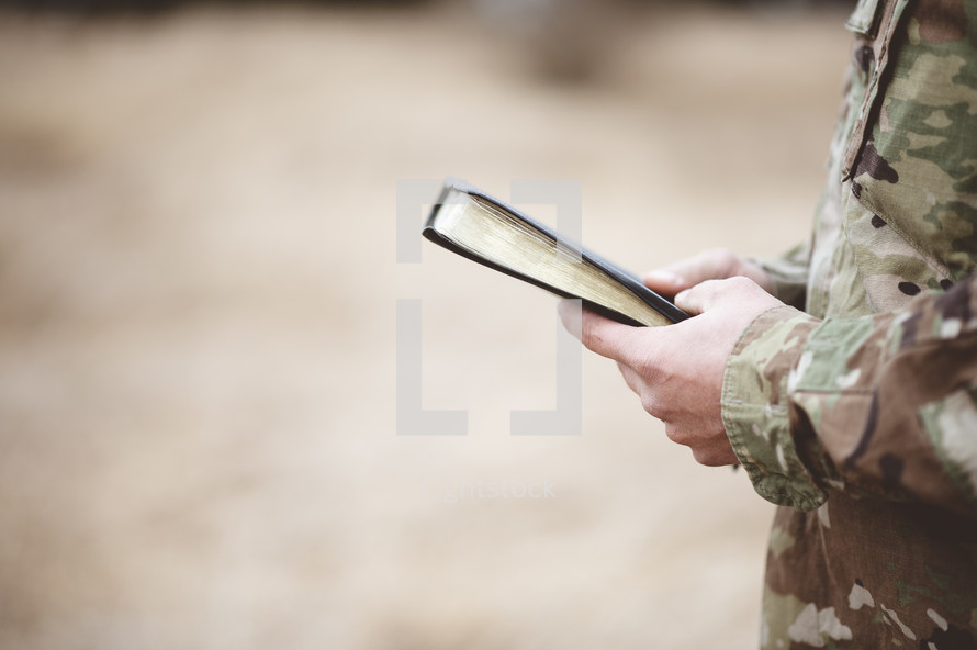 Christian soldier in a field praying holding a Bible