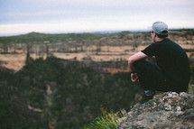 Man sitting on the edge of a canyon.
