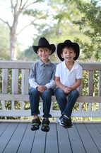 Young brothers sitting on a porch swing wearing cowboy hats