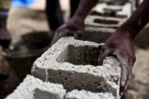 A man uses cinder block to build a wall on a new church