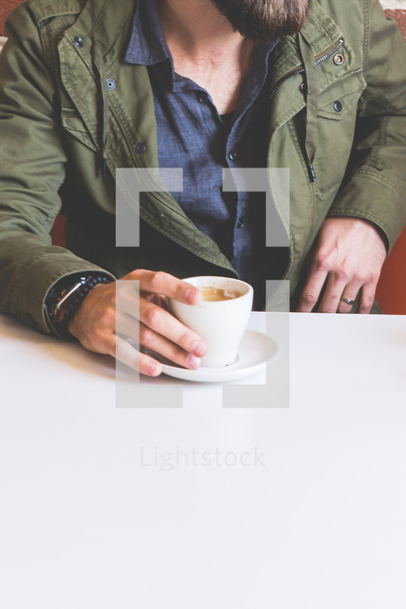 man's hand on a cup of coffee