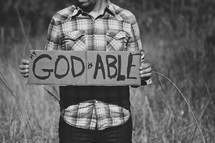 man holding a sign with the words God is able