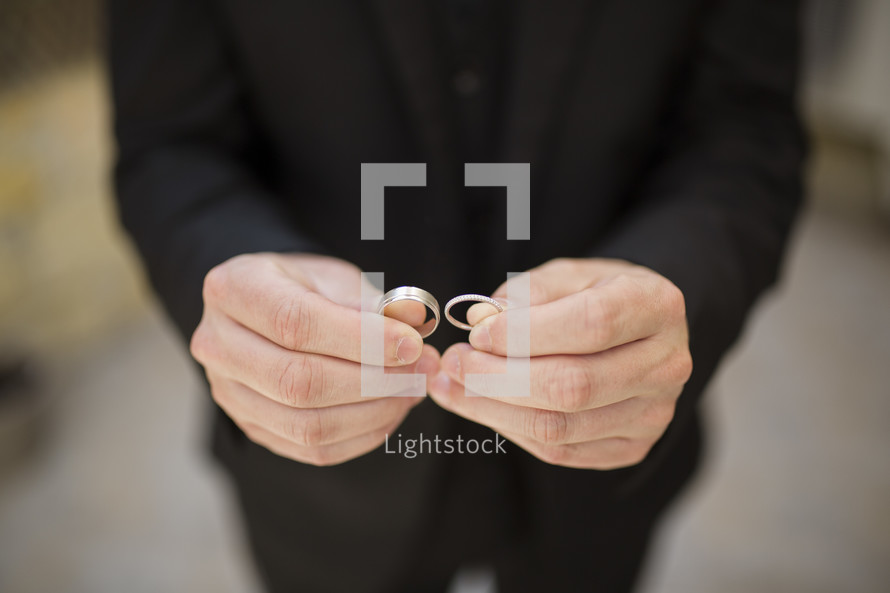 groom in a tuxedo holding wedding rings