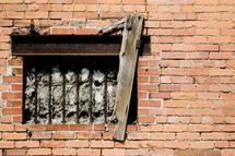 bared window on a brick wall