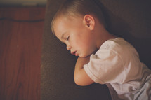 a toddler napping on a couch