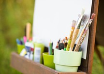 easel and art supplies with a blank canvas