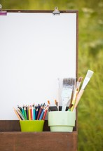 easel, art supplies, and blank canvas outdoors