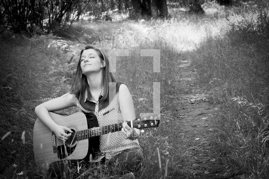 woman playing a guitar while sitting in a a field