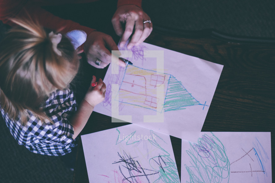 Mother and daughter drawing with crayons.