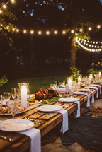 An long outdoor table set for an evening dinner party.