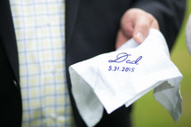 """A groom holding a handkerchief embroidered with, """"Dad, 5.31.2015."""""""