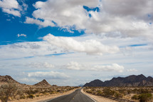 highway through desert and mountains - cloud filled sky